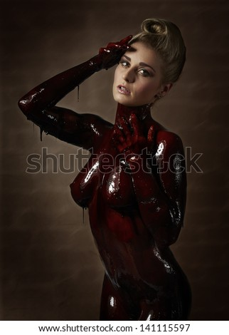 Beautiful and sexy caucasian young adult woman covered in sweet running chocolate - stock photo