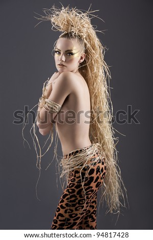 beautiful and sexy girl with raffia hair and a ethnic jungle costume in a shot over dark with creative make up - stock photo