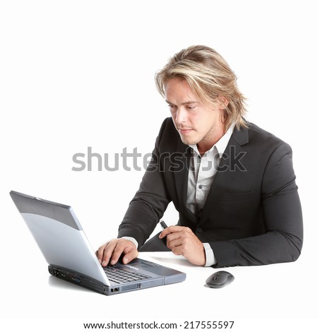 beautiful and sexy man is working behind his laptop computer at the office - stock photo