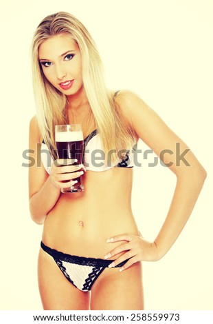 Beautiful and sexy woman in lingerie drinking beer. - stock photo