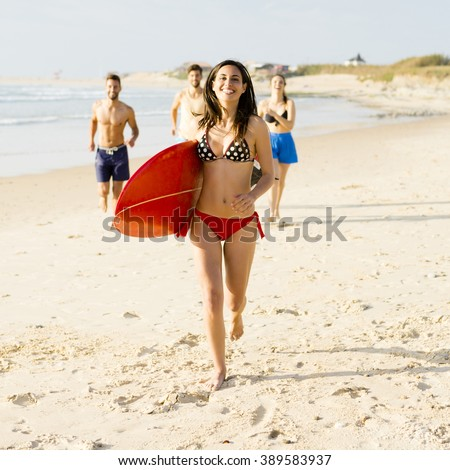 Beautiful and sexy woman running at the beach with her surfboard - stock photo