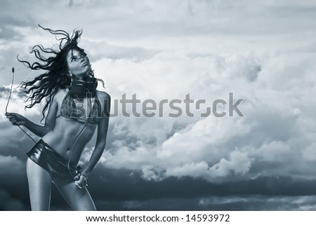 Beautiful and sexy woman with headphones on her neck posing against cloudy sky. Concept - music in the air - stock photo