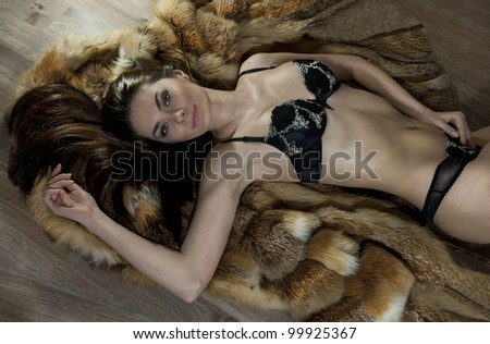Beautiful and sexy young woman in underwear laying down on floor and covering with fur - stock photo