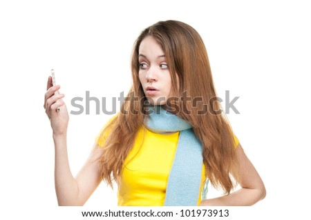 Beautiful and shocked or surprised young student girl holding cell phone in her hand. Looking at the phone. Isolated on white background. - stock photo