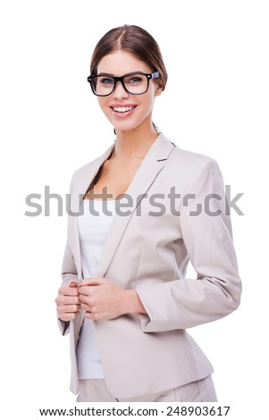 Beautiful and smart. Confident young businesswoman adjusting her jacket and smiling while standing against white background - stock photo