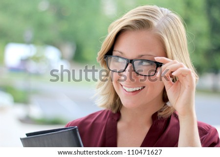 Beautiful and Smiling Business Woman Wearing Eye Glasses Looking To The Side - stock photo