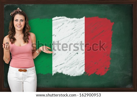 Beautiful and smiling woman showing flag of Italy on blackboard, presentation for tourism and marketing research - stock photo