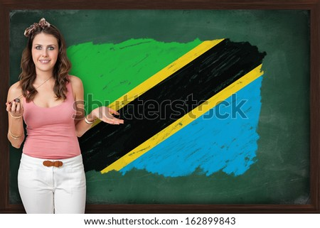 Beautiful and smiling woman showing flag of Tanzania on blackboard, presentation for tourism and marketing research - stock photo
