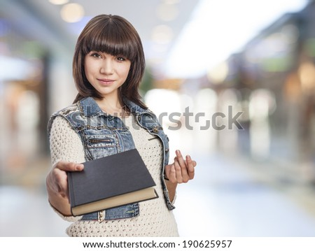 beautiful and smiling young woman giving a book - stock photo