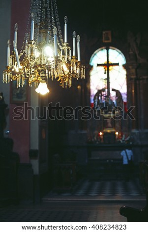 Beautiful and spiritual baroque church interior with focus on old chandelier - stock photo