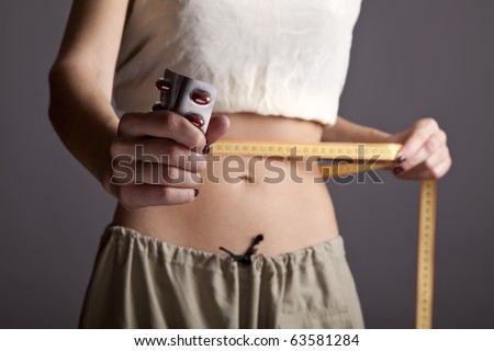 Beautiful and strong women's abs with metre and pills. Studio shot. - stock photo