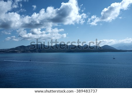 Beautiful and tranquil sea landscape with visible coastline. Scene is captured from one of the most beautiful Mediterranean islands in Greece. - stock photo