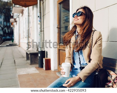Beautiful and young girl in a coat and scarf and sunglasses sitting on the bench. Woman drinking coffee and laughing. Summer. - stock photo