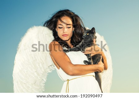 beautiful angel woman against sky with cat in her arms - stock photo