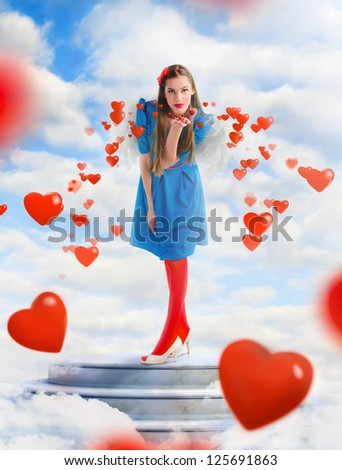 Beautiful angel woman blowing  red hearts from the sky - stock photo