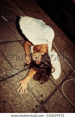 beautiful angel woman with white wings lie on roof - stock photo