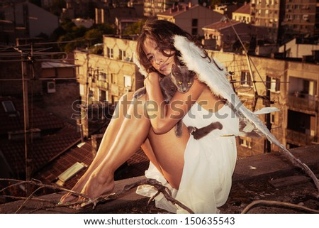 beautiful angel woman with white wings sit on roof edge holding cat, view of the city  in background - stock photo