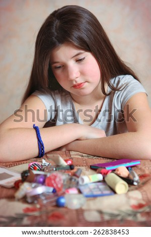 beautiful angry preteen girl with cosmetic at the table - stock photo
