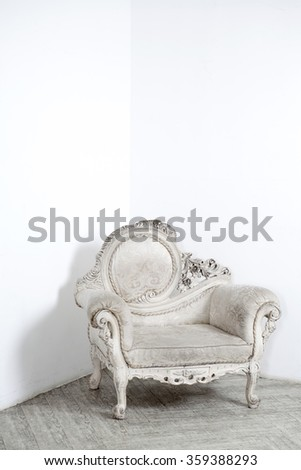 Beautiful antic armchair from solid wood in white interiour - stock photo