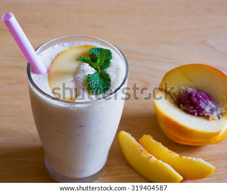 Beautiful appetizer peach fruit smoothie. Yogurt cocktail. Close up. Natural detox. Liquid ice cream. Rustic nature style. - stock photo