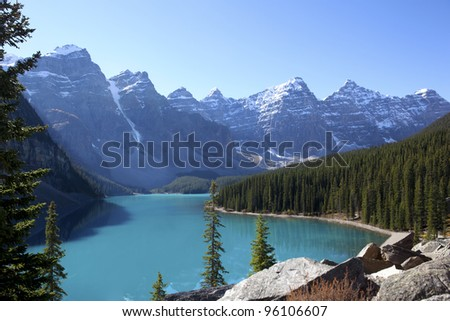 Beautiful aqua colored lake with mountains in background. - stock photo