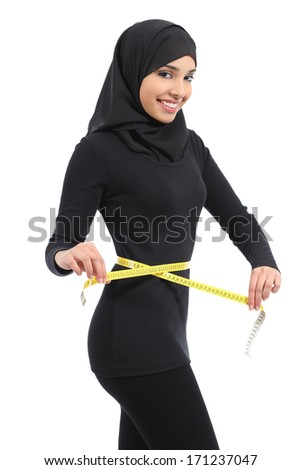 Beautiful arab saudi fitness woman measuring her waist with a tape measure and looking at camera isolated on a white background               - stock photo