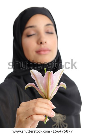 Beautiful arab woman wearing a hijab smelling a flower isolated on a white background           - stock photo