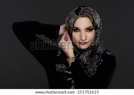 Beautiful Arab Woman Wearing Abaya on gray background - stock photo
