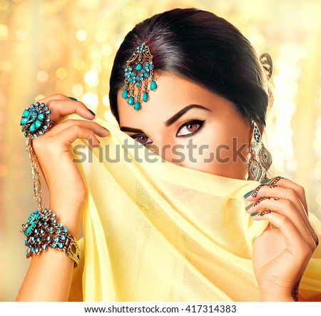 Beautiful Arabian woman portrait. Young Hindu woman with mehndi tattoos from black henna on her hands. Portrait of beauty Indian model with bright make-up who hiding her face behind the veil Over gold - stock photo