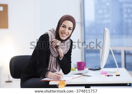 Beautiful Arabic business woman writes in a notebook in her office - stock photo