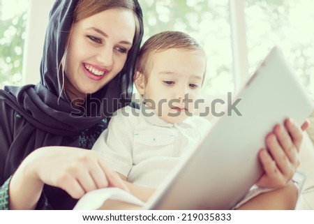 Beautiful Arabic family, mother and cute baby with tablet - stock photo
