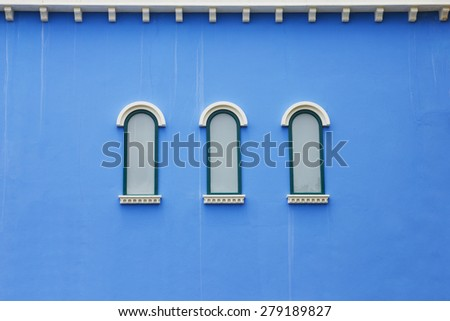 Beautiful arched window on blue wall background wallpaper design - stock photo