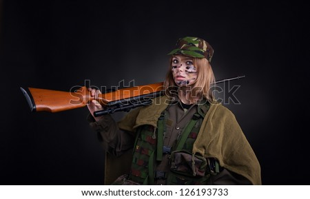 Beautiful army girl, soldier woman with rifle military uniform over black background - stock photo