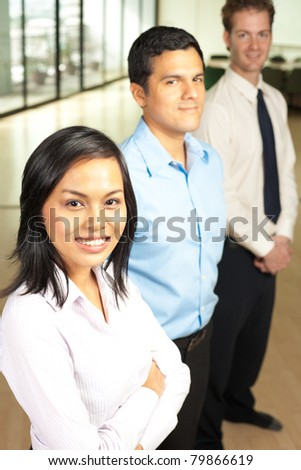 Beautiful Asian business woman and her male Hispanic and Caucasian colleagues stand behind in a row in a corporate office setting, smiling looking at camera. Vertical - stock photo