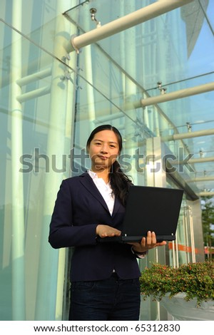 beautiful asian business woman at office building with laptop computer - stock photo