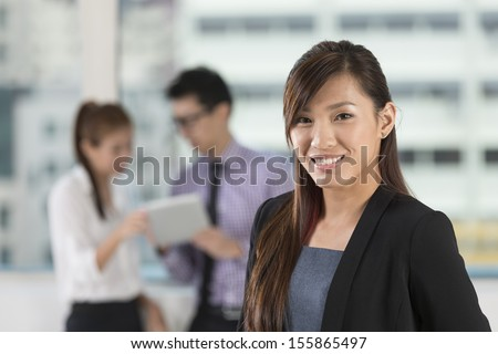 Beautiful Asian business woman standing with her staff in background - stock photo