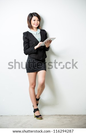 Beautiful Asian business woman using tablet computer. Full length shot, leaning against a white wall. - stock photo