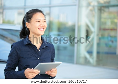 beautiful asian businesswoman use digital tablet leaning on car outside of office building - stock photo