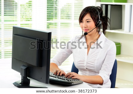 Beautiful Asian Female Call Center Agent Wearing A Telephone Headset Using A Computer - stock photo
