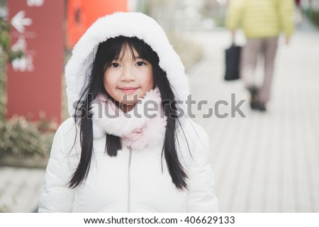 Beautiful asian girl in winter coat outdoors,vintage filter - stock photo