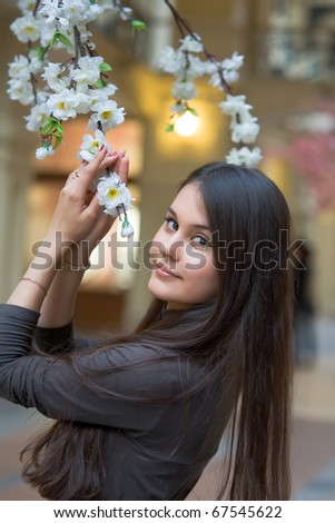 Beautiful Asian girl near a flowering apple tree - stock photo