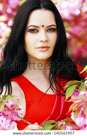 beautiful asian indian woman in the park on a warm spring day with blossom flowers around her - stock photo