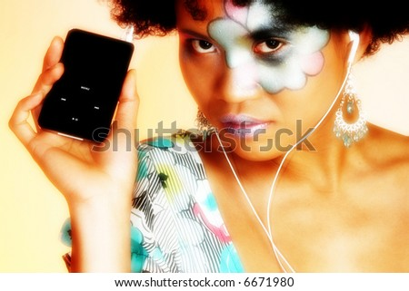 Beautiful Asian Indonesian woman with artistic make-up and digital music player. - stock photo