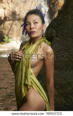 Beautiful Asian model standing in front of scenic waterfall in Thailand park wearing silky green fabric covering her body on sunny day. - stock photo