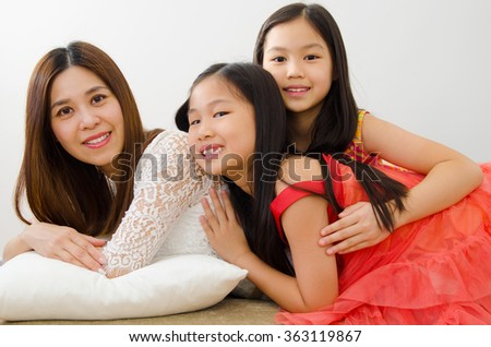Beautiful asian mother and children lying on sofa - stock photo