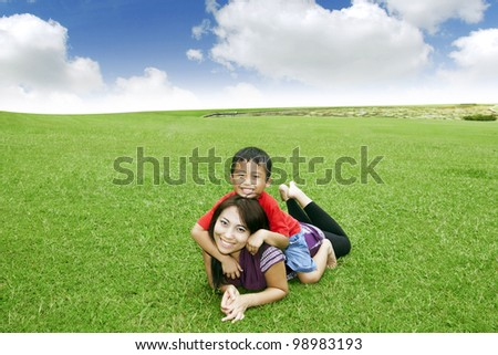 Beautiful Asian mother smiling with her cute son in meadow - stock photo
