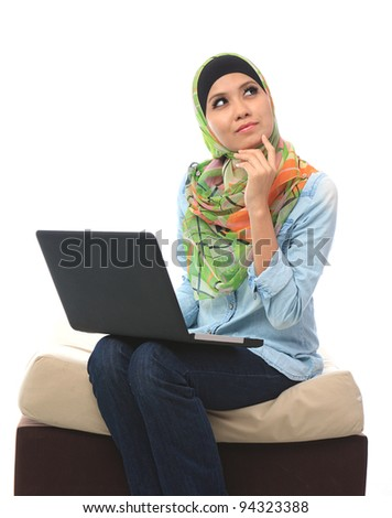 Beautiful asian muslim woman sitting in front of laptop and thinking - stock photo