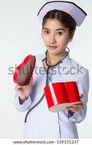 beautiful asian nurse holding a symbol of heart - stock photo