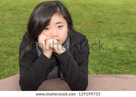 Beautiful Asian teenage female with expressive sad eyes resting her head in her hands and elbows on picnic table in park - stock photo