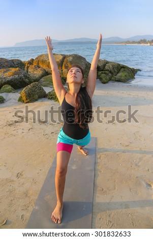 Beautiful asian woman doing yoga on the beach - stock photo